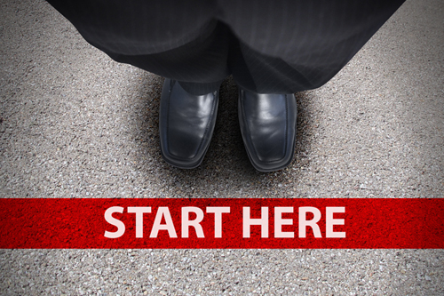 "A partial image of a man standing behind a line on the ground that says ""Start Here"""