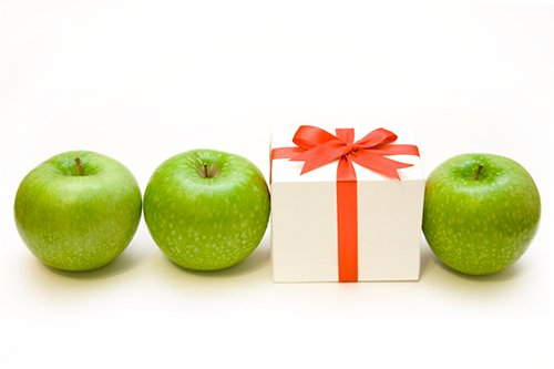 A row of three green apples with a package between two of them