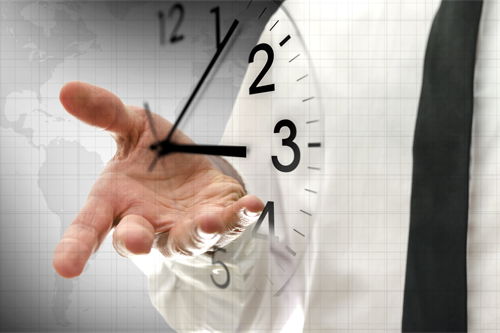 A mans hand is reaching toward a transparent clock