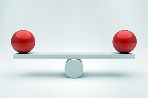 Two red balls balanced on either end of a beam