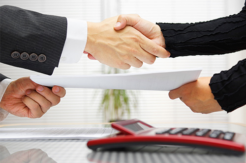 A lawyer shakes hands with a legal secretary after negotiating salary