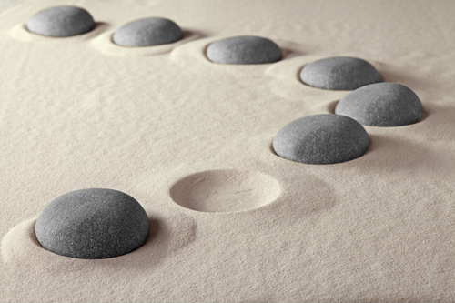 A series of stones arranged in the sand with an indentation where one is missing