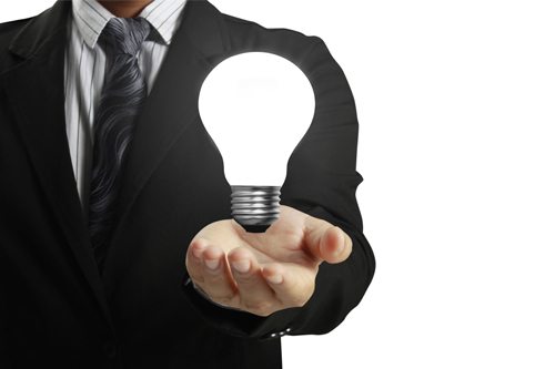 A light bulb hovering over a mans outstretched hand