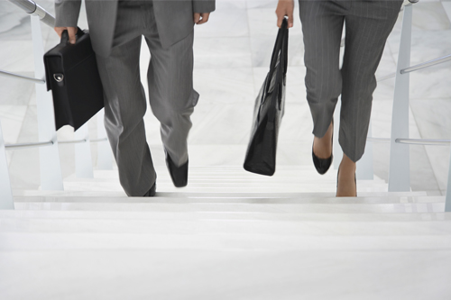 Two corporate lawyers are walking up some steps together