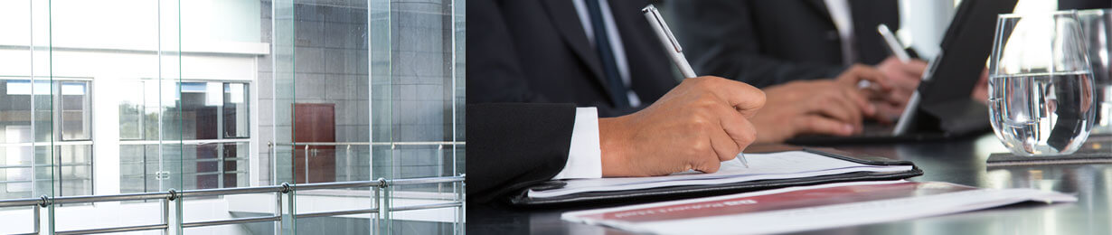 Businessmen take notes at a conference room table