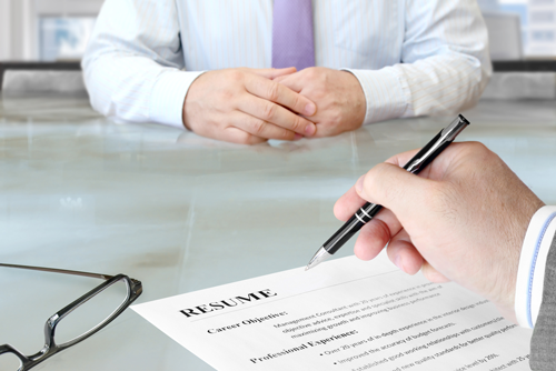 A partial image of an employer looking over a candidates legal resume