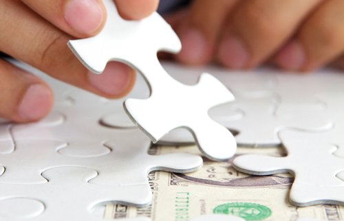 A hand places the final piece of a puzzle, under which is a dollar bill