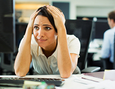 A stressed woman has her hands on her head