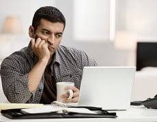 A businessman sitting behind a computer could ease his frustrations by using an IT staffing agency to find quality employees