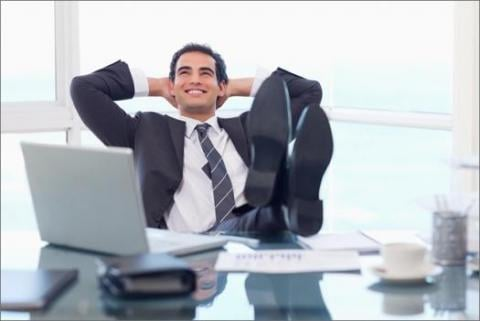 A happy payroll worker with his feet up on his desk because he works at the best workplace