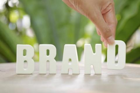 "A hand uses letters to spell ""brand"" and emphasize the importance of employer branding"