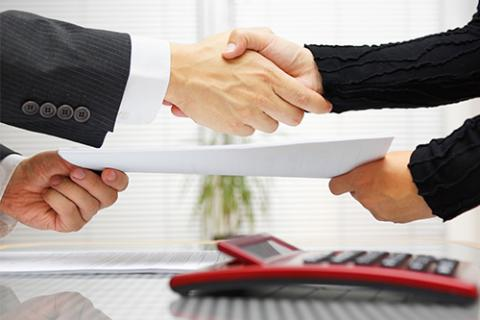 A lawyer and legal secretary shake hands after negotiating a salary