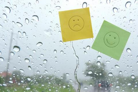 Image of a frowning face and a smiling face on a window