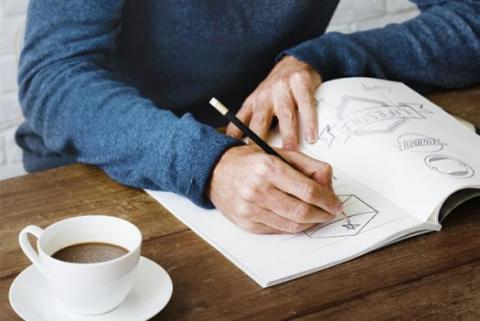 A creative professional sketching in a coffee shop