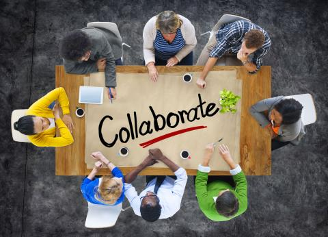 Table of people at table that says collaborate