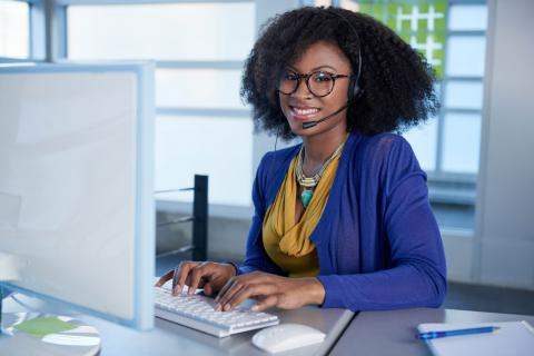 How to Become a Medical Credentialing Specialist — Woman with glasses and a headset sitting at a desk with a computer