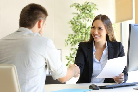 Female hiring manager shaking hands with a male job applicant.