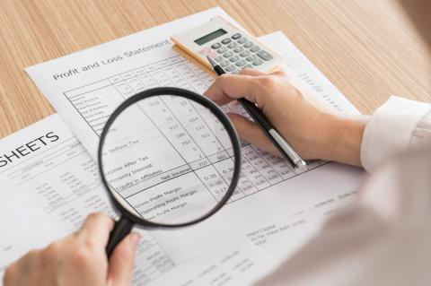 Working in internal auditing with magnifying glass, spreadsheets