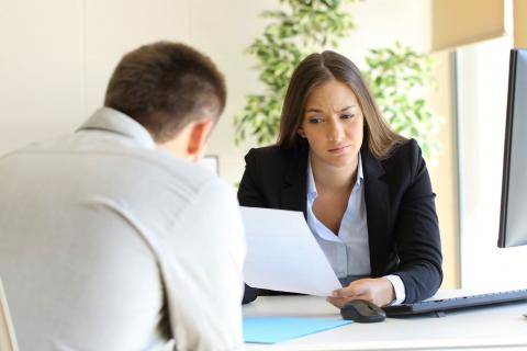 Hiring manager frowning at candidate's resume mistakes