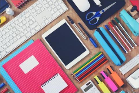 How to Organize Your Desk for Maximum Efficiency — desk filled with pens, keyboard, notebooks, scissors, ruler