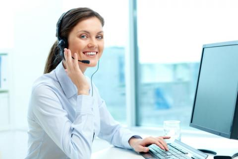 A smiling receptionist talks at the phone at her desk