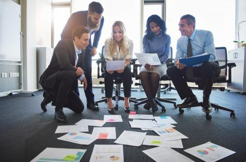 Group Of Professionals Displaying Their Accounting Skills With Lots Of Paper