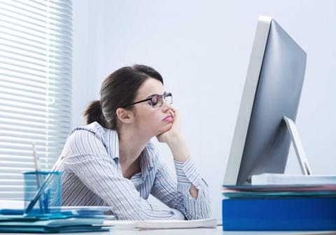 Young woman facing a computer and looking bored.