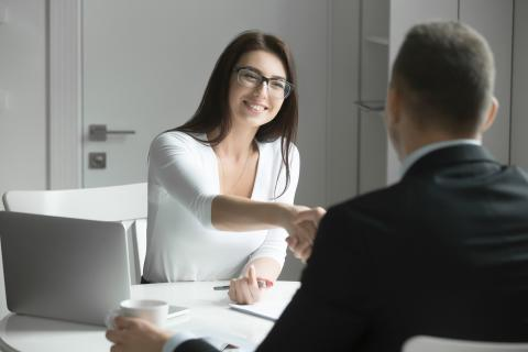 Two people shaking hands at desk, as a financial controller is hired