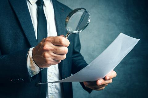 Man with magnifying glass busy with forensic accounting jobs