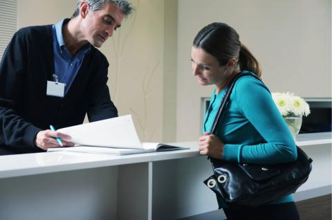 Female patient checking in at the front desk with a male patient registration clerk.