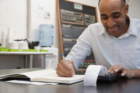 Man in office with adding machine contemplating small business hires