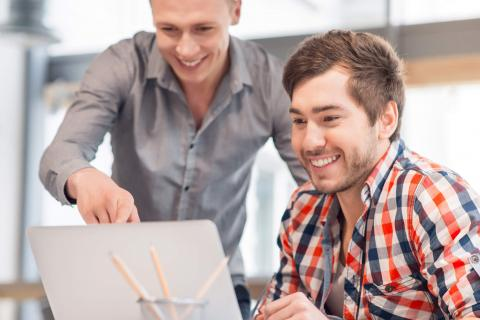 Two young, smiling IT professionals looking at a laptop.