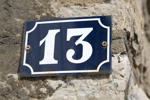 A sign with the number 13 on it, attached to a stone wall.