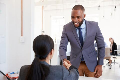 Young professional man shaking hands with a woman.