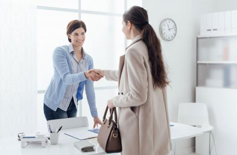 A female hiring manager shaking hands with a female job candidate.