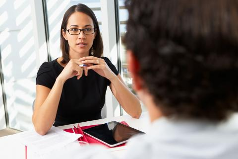 Businesswoman interviewing male job candidate.