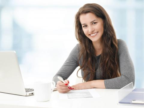 Administrative Professionals Day: An Opportunity to Say Thank You — smiling woman holding a pen and in front of a laptop