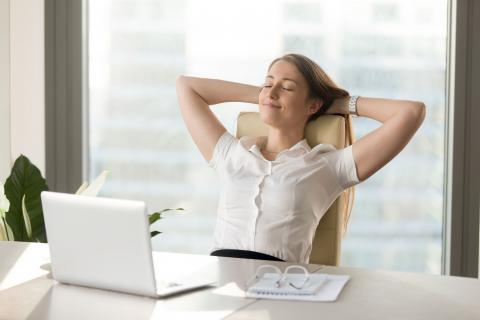 Woman at laptop looking relaxed about getting back to work after a leave