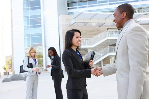 4 Top Hiring Strategies to Overcome Challenges in the Market — two people shake hands outside office building