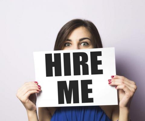 "Job seeker holding a ""Hire Me"" sign."