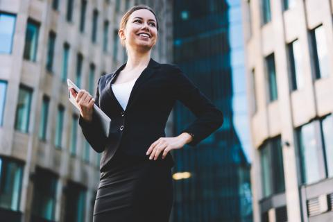 Happy woman in city who has earned accounting certifications