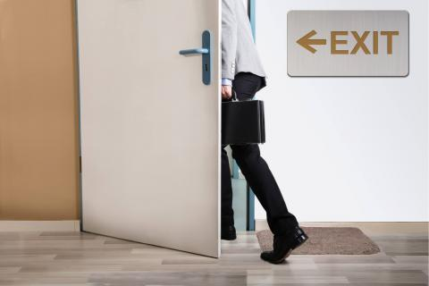 Image of a new employee leaving through a door next to an exit sign.