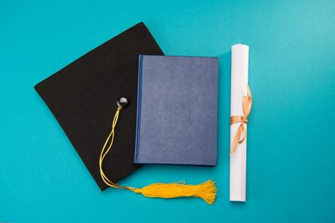 Image of a graduation cap, a book and a diploma.