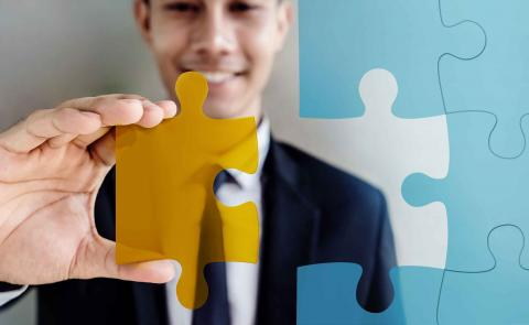 Man with puzzle piece showing how to hire employees who fit
