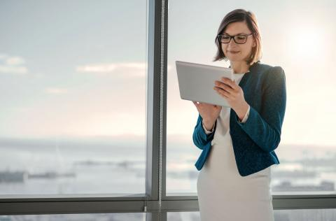 Woman standing near window with tablet working as a payroll manager
