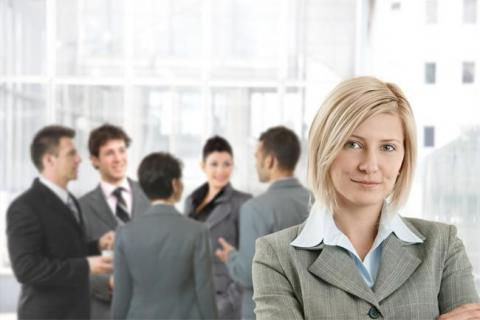 Woman in front of group of professionals as she considers her senior accountant salary