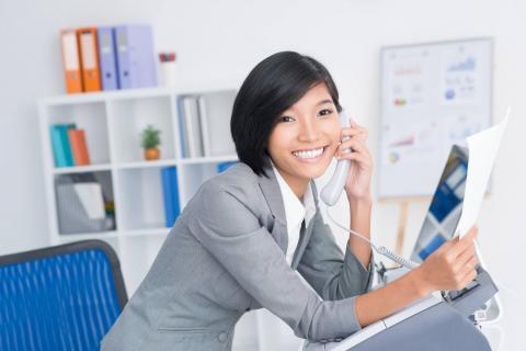 Smiling administrative assistant on the phone and holding a certification.