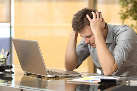 Worker at laptop with head in hands demonstrating lack of employee motivation