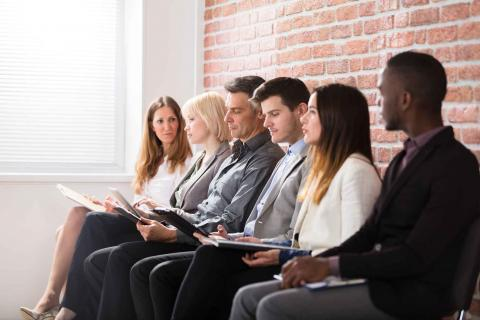 7 Things to Look for When Hiring a Payroll Specialist. Six people sitting in front of a brick wall waiting to be called for an interview.