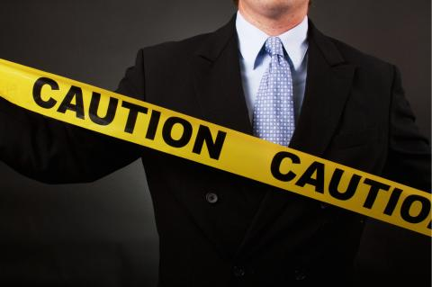 A person holding caution tape to warn hiring managers against making a bad hire.